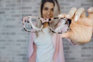person holding up pink glasses