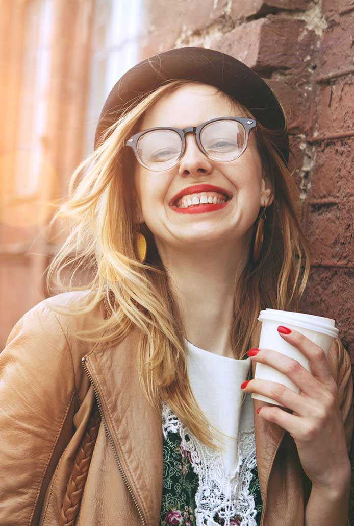 girl wearing glasses and holding a coffee cup