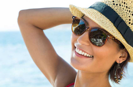 lady wearing prescription sunglasses and hat in the sun